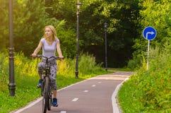 Mujer joven que monta una bicicleta Imágenes de archivo libres de regalías