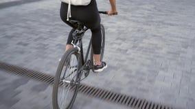 Mujer joven que monta una bicicleta al aire libre almacen de video