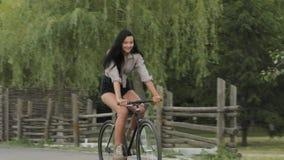 Mujer joven que monta una bicicleta al aire libre metrajes