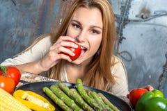 Mujer joven que muerde un tomate Imagenes de archivo
