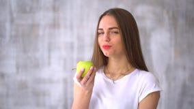 Mujer joven que muerde y que come la manzana verde sabrosa Mujer joven sana que come la manzana verde y que sonríe en casa - dent metrajes