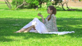 Mujer joven que muerde y que come la manzana verde sabrosa almacen de video