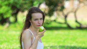 Mujer joven que muerde y que come la manzana verde sabrosa metrajes