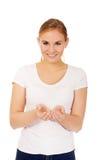 Mujer joven que muestra algo en la palma abierta Imagen de archivo