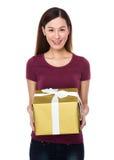 Mujer joven que muestra con el giftbox Fotos de archivo