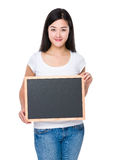 Mujer joven que muestra con la pizarra Imagen de archivo libre de regalías