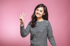 Mujer joven que muestra cuatro fingeres en fondo rosado imágenes de archivo libres de regalías