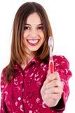 Mujer joven que muestra el cepillo de dientes Foto de archivo