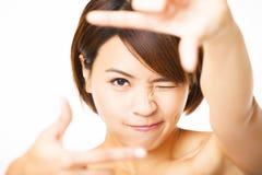 Mujer joven que muestra el finger del marco Imágenes de archivo libres de regalías