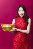 mujer joven que muestra el oro por Año Nuevo chino Fotografía de archivo