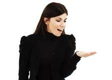 Mujer joven que muestra el producto con la palma abierta de la mano Foto de archivo
