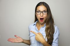 Mujer joven que muestra el producto con la palma abierta de la mano y que señala el finger Expresión emocionada sobre los vidrios fotografía de archivo libre de regalías