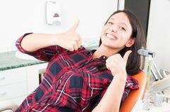 Mujer joven que muestra el pulgar para arriba en silla del dentista Imagen de archivo libre de regalías