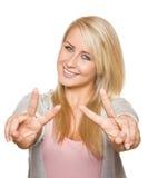 Mujer joven que muestra el signo de la paz con sus manos Imagen de archivo libre de regalías