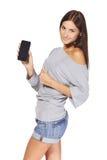 Mujer joven que muestra el teléfono celular móvil Imágenes de archivo libres de regalías