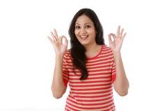 Mujer joven que muestra gesto del thumbsup contra blanco Fotografía de archivo libre de regalías