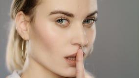 Mujer joven que muestra la muestra del silencio Muchacha rubia que pone el finger en boca en estudio almacen de metraje de vídeo