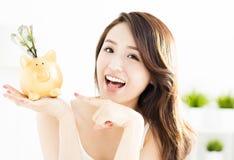 Mujer joven que muestra la hucha con el dinero Foto de archivo