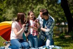 Mujer joven que muestra las fotos a su marido y a su hija mientras que se sienta en la manta en el parque fotos de archivo
