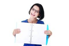 Mujer joven que muestra las paginaciones en blanco de su cuaderno imágenes de archivo libres de regalías