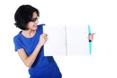 Mujer joven que muestra las paginaciones en blanco de su cuaderno fotos de archivo libres de regalías