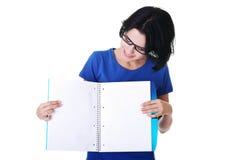Mujer joven que muestra las paginaciones en blanco de su cuaderno fotografía de archivo