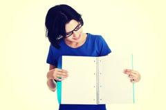 Mujer joven que muestra las paginaciones en blanco de su cuaderno imagen de archivo