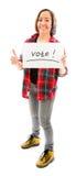 Mujer joven que muestra los pulgares para arriba con la muestra del voto Imagen de archivo