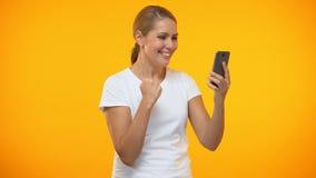 Mujer joven que muestra sí el mensaje del smartphone de la lectura del gesto, buenas noticias, app apostado metrajes