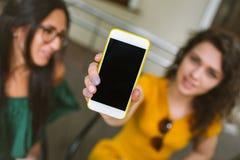 Mujer joven que muestra smartphone en cámara al aire libre Fotografía de archivo