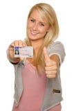 Mujer joven que muestra su licencia de conductor Imagenes de archivo