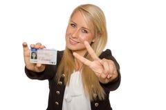 Mujer joven que muestra su licencia de conductor Foto de archivo libre de regalías