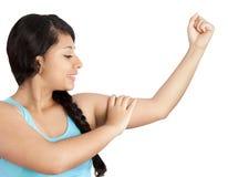 Mujer joven que muestra sus músculos Foto de archivo