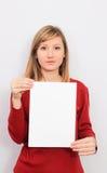 Mujer joven que muestra una hoja de papel en blanco Foto de archivo libre de regalías