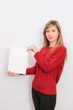 Mujer joven que muestra una hoja de papel en blanco Imágenes de archivo libres de regalías