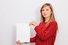 Mujer joven que muestra una hoja de papel en blanco Imagen de archivo libre de regalías