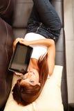 Mujer joven que muestra una PC de la tablilla Imágenes de archivo libres de regalías