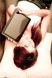 Mujer joven que muestra una PC de la tablilla Imagenes de archivo