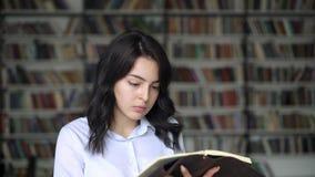 Mujer joven que mueve de un tirón a través de un libro en el fondo de los estantes de la biblioteca metrajes