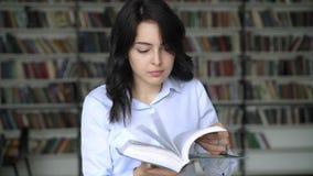 Mujer joven que mueve de un tirón a través de una enciclopedia en el fondo de los estantes de la biblioteca almacen de video