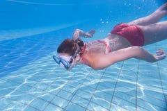 mujer joven que nada bajo el agua en una piscina Imagenes de archivo