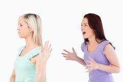 Mujer joven que no hace caso de una señora gritadora Foto de archivo