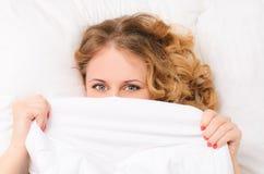 Mujer joven que oculta debajo de la manta blanca Foto de archivo