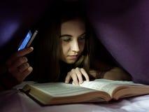 Mujer joven que oculta debajo del libro interesante de la lectura combinada y arrobada en la noche Iluminación de la muchacha con Fotografía de archivo libre de regalías