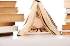 Mujer joven que oculta detrás de un libro Fotos de archivo