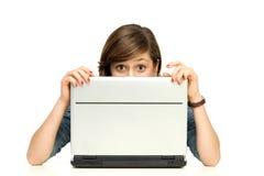 Mujer joven que oculta detrás de una computadora portátil Imágenes de archivo libres de regalías