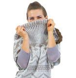 Mujer joven que oculta en escote del suéter Imagenes de archivo