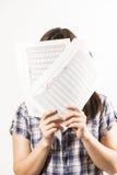 Mujer joven que oculta su cara detrás de las hojas de papel Fotos de archivo libres de regalías