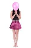 Mujer joven que oculta su cara detrás del globo rosado Imágenes de archivo libres de regalías