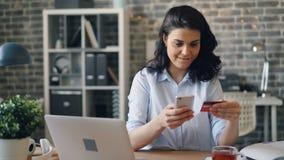 Mujer joven que paga en línea con la tarjeta de crédito usando smartphone en lugar de trabajo almacen de video